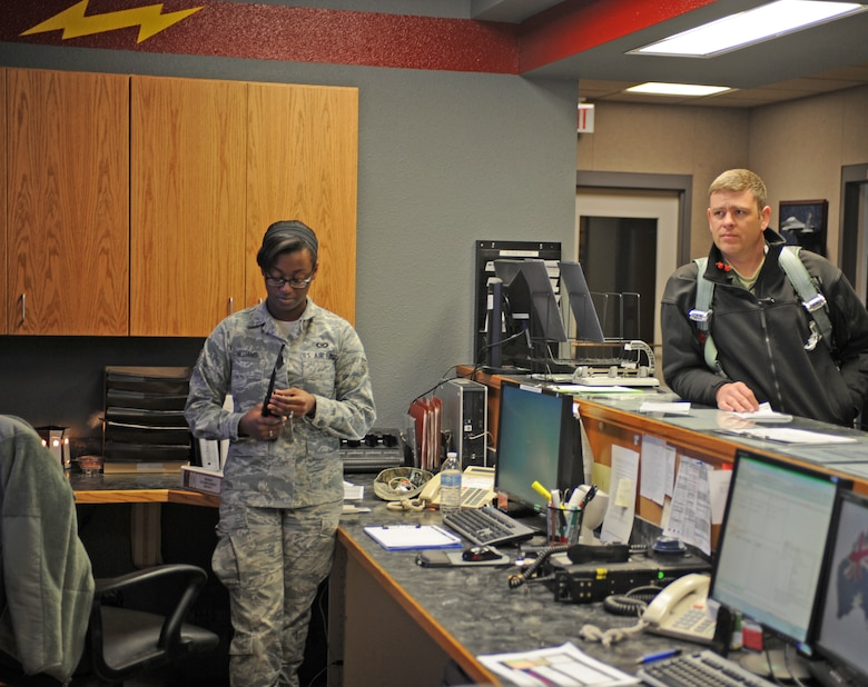 U.S. Air Force Senior Airman Casiana Curry-Williams, 389th Fighter Squadron aviation resource manager and Lt. Col. Albert Kennedy, 366th Fighter Wing Command Post chief, wait for the morning pre-flight brief to finish March 18, 2013, at Mountain Home Air Force Base, Idaho. Squadron aviation resource managers are responsible for maintaining aircrew records and monitoring daily flight mission data. (U.S. Air Force photo/Senior Airman Benjamin Sutton)