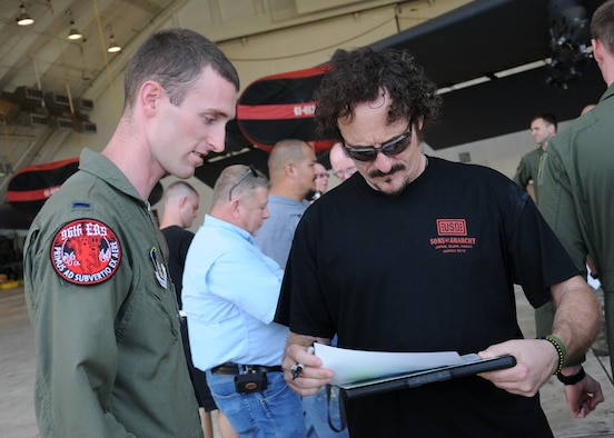 "Kim Coates, ""Sons of Anarchy"" actor, signs an autograph for 1st Lt. Eric Poole, 96th Expeditionary Bomb Squadron pilot, at Hangar 1 on Andersen Air Force Base, Guam, March 16, 2013. The actors visited the base as part of a weeklong United Service Organization tour which also took them to military installations in Japan and Hawaii. (U.S. Air Force photo by Staff Sgt. Melissa B. White/Released)"