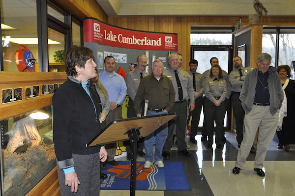 Carolyn Bauer, a former Lake Cumberland park ranger who recently retired from the Corps in March with 35 years of service, talks March 13, 2013 as an honorary display wall is unveiled to commemorate the service of park rangers at the Lake Cumberland Visitor's Center. She called Wallace Halcomb, who was honored, a great teacher, a mentor and a fun-loving family man.   Current and former park rangers, employees, family members and friends commemorated the service of park rangers over the decades as environmental regulators and guardians of historic lands.