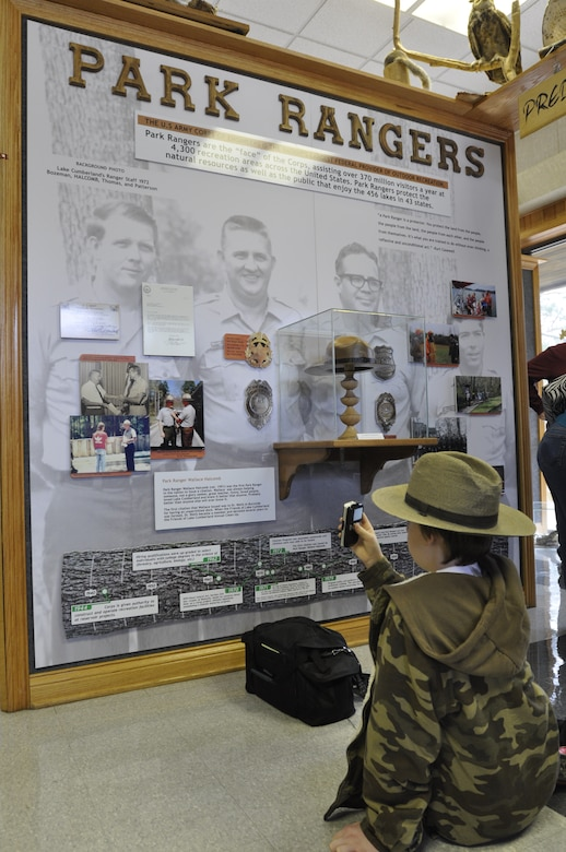 Jacob Halcomb, 11, the grandson of Park Ranger Wallace Halcomb, wears his grandfather's original ranger hat and badge as he looks at an honorary display wall March 13, 2013 to commemorate the service of Park Ranger Wallace Halcomb and park rangers at the Lake Cumberland Visitor's Center.