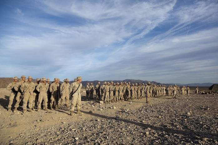 The U.S. Marines of Company A, 1st Battalion, 4th Marines, 5th Marine Regiment, stand in formation following range 410 on Marine Corps Air Ground Combat Center Twentynine Palms, Calif., Dec. 1, 2012. Range 410 is a platoon fire and maneuver exercise held as part of Exercise Steel Knight. Exercise Steel Knight is an annual training exercise held to demonstrate the 1st Marine Division's abilities in a simulated combat scenario. (U.S. Marine Corps photo by Cpl. Jonathan R. Waldman/Released)