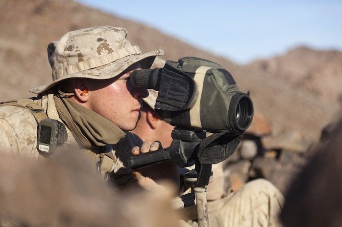 U.S. Marine Corps Pfc. Ben Downing, assistant radio operator with scout sniper team 1, scout sniper platoon, 1st Battalion, 4th Marines , 5th Marine Regiment, uses a spotting scope to determine shot distances during range 401 on Marine Corps Air Ground Combat Center Twentynine Palms, Calif., Dec. 4, 2012. Range 401 is a company maneuver and fire exercise held as part of Exercise Steel Knight. Exercise Steel Knight is an annual training exercise held to demonstrate the 1st Marine Division's abilities in a simulated combat scenario. (U.S. Marine Corps photo by Cpl. Jonathan R. Waldman/Released)