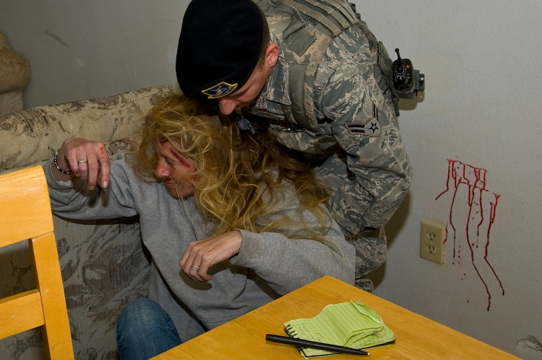 U.S. Air Force Airman 1st Class Lorenzo Garcia, an installation entry controller of 1st Special Operations Security Forces Squadron, assists a simulated domestic violence victim during domestic violence training at base housing on Hurlburt Field, Fla., March 14, 2013. Mock injuries were created using moulage to generate realistic training scenarios where medical response might be necessary. (U.S. Air Force photo by Airman 1st Class Michelle Vickers)