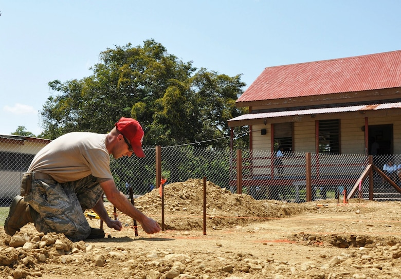 Staff Sgt. Justin Jones, heavy equipment operator for the 823rd RED HORSE Squadron, lays out string Mar. 18, 2013, in Crooked Tree, Belize, to measure the footer for the edge of the foundation at the construction site of the future Crooked Tree Government Primary School. Civil Engineers from both the U.S. and Belize will construct various structures at schools throughout Belize as part of an exercise called New Horizons. Building these facilities will support further education of the children in the country. (U.S. Air Force photo/Capt. Holly Hess).