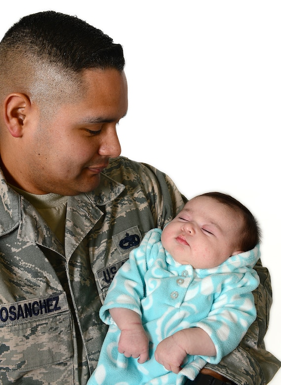 ROYAL AIR FORCE LAKENHEATH, England – Tech. Sgts. Ruben TrejoSanchez, 493rd Aircraft Maintenance Unit NCO in charge of weapons maintenance, holds his first child, Alexis Quinn March 19, 2013. TrejoSanchez delivered his baby at home during Super Bowl weekend. (U.S. Air Force photo by Staff Sgt. Stephanie Mancha)