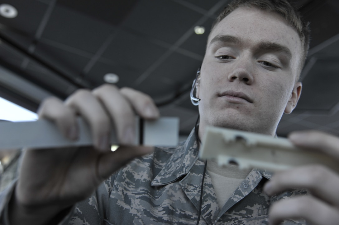 Airman 1st Class Seth Lewis, 509th Operations Support Squadron air traffic control apprentice, slides a flight strip into a holder at Whiteman Air Force Base, Mo., March 11, 2013. A flight strip is used for flight planning to tell route of flight. It also tracks the arrival and departure times. (U.S. Air Force photo by Airman 1st Class Keenan Berry/Released)
