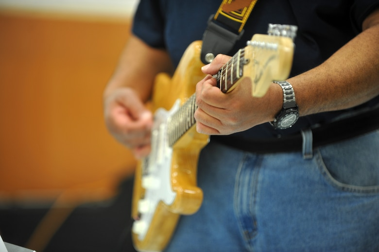 Ivan Taylor, Vets in Tune rhythm guitarist, plays a riff during a performance March 15, 2013, in the food court area at The Exchange on Buckley Air Force Base, Colo. Vets in Tune is a band of disabled veterans from the Denver area. (U.S. Air Force photo by Airman 1st Class Riley Johnson/Released)
