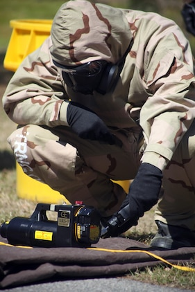 Marine with Explosive Ordnance Disposal and Chemical, Biological, Radiological, and Nuclear Defense decontaminate gear during a joint training exercise, March 8. Some of the procedures Marines might execute during a chemical, biological, radiological, and nuclear attack include detection, sampling, identification and neutralization of hazardous materials and chemicals, extraction of contaminated personnel, technical and mass decontamination, and sensitive site exploitation.