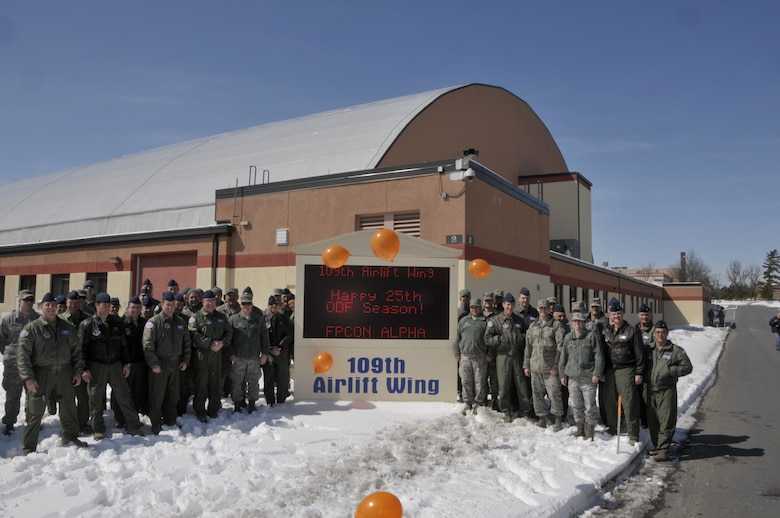 109th Airlift Wing members pose for a photo at the unit's sign in celebration of the unit's 25th year flying missions to Antarctica in support of Operation DEEP FREEZE at Stratton Air National Guard Base on March 21st, 2013. (USAF Photo by MSgt Willie Gizara/Released).