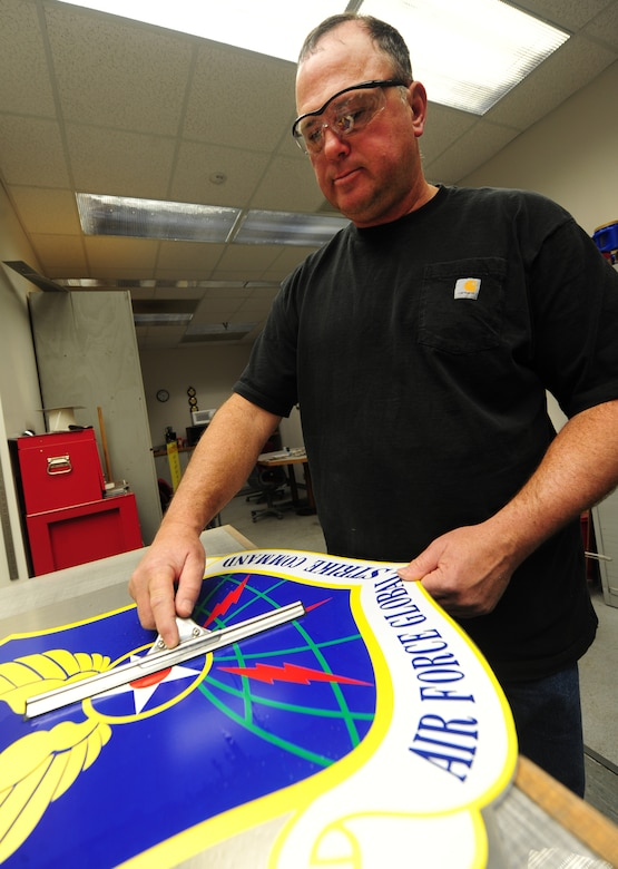 Bernard Jones, 509th Civil Engineer Squadron sign maker, cleans an Air Force Global Strike Command sign at Whiteman Air Force Base, Mo., March 11, 2013. Signs of MAJCOMs, such as this one, are posted at the front gate to identify the command to drivers as the pass by. (U.S. Air Force photo by Staff Sgt. Nick Wilson/Released)