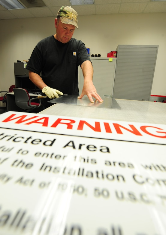 Bernard Jones, 509th Civil Engineer Squadron sign maker, prepares a restricted area sign for vinyl coating at Whiteman Air Force Base, Mo., March 11, 2013. The vinyl coating acts as an adhesive that enables personnel to attach the banner to the aluminum sign frame.  (U.S. Air Force photo by Staff Sgt. Nick Wilson/Released)