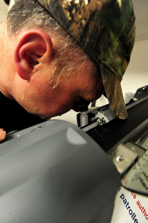 Bernard Jones, 509th Civil Engineer Squadron sign maker, uses the sight scope of a plotter machine to ensure the blade is properly lined up with the material being cut, March 11, 2013. The signs Jones creates are used for everything from office entryway signs to restricted area signs on the flightline. (U.S. Air Force photo by Staff Sgt. Nick Wilson/Released)