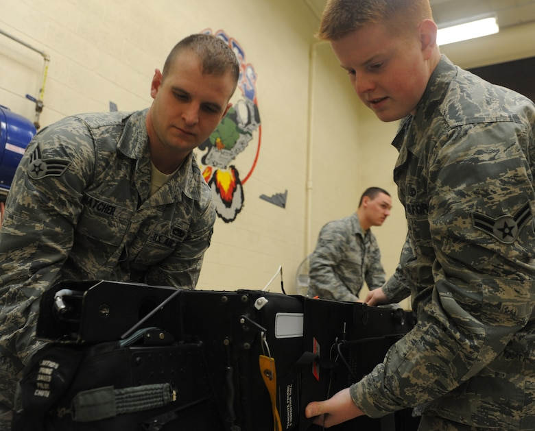 Senior Airman Patrick Hatcher and Airman 1st Class Christopher Amsel, 509th Maintenance Squadron egress systems journeymen, inspect a training ejection seat at Whiteman Air Force Base, Mo., March 19, 2013. The egress shop works on all ejection seats for Whiteman's B-2 Spirit and T-38 Talon aircraft. (U.S. Air Force photo by Airman 1st Class Bryan Crane/Released)