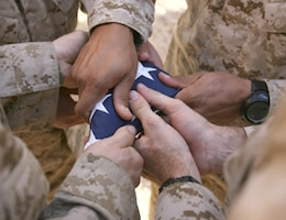 Marines fold a flag in honor of fallen comrades.