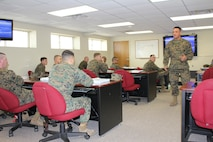 Staff Sergeant John Herrera presents instruction on United States Marine Corps uniform regulations to Corporals Course students.