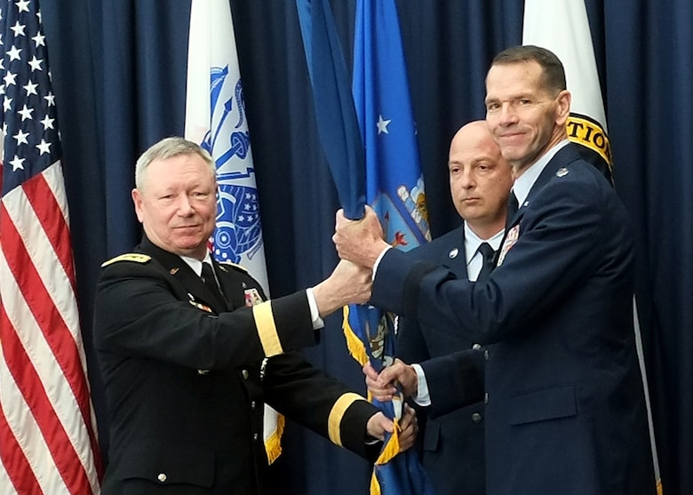 """Lt. Gen. Stanley """"Sid"""" Clarke III, right, the director of the Air National Guard, receives the organizational colors of the Air National Guard from Army Gen. Frank Grass, chief, National Guard Bureau, during a ceremony at the Air National Guard Readiness Center at Joint Base Andrews, Md., where Clarke assumed the responsibilities of his current position, Friday, March 22, 2013. Clarke takes over the duties of director from Air Force Lt. Gen. Harry """"Bud"""" Wyatt, who recently retired. (U.S. Army photo by Sgt. 1st Class Jon Soucy)"""