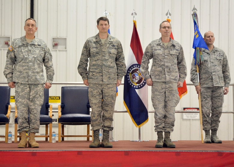 Missouri National Guard adjutant general, Maj. Gen. Stephen Danner, incoming 131st Bomb Wing commander, Col. Mike Francis, Missouri National Guard assistant adjutant general-air, Col. Greg Champagne, and 131st Bomb Wing Command Chief Master Sgt. Rich Pingleton stand at attention while the order is published at the change of command ceremony at Whiteman AFB., March 3.  (National Guard Photo by Staff Sgt. Sean Navarro)