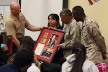 Colonel Scott Loch, Marine Corps Activity Guam Commanding Officer, far left, hands a framed plaque in appreciation to the principal, Faye Flores, center, Master Sgt. Larry McNair, middle right, and Chief Warrant Officer 4 Ernest Turner, far right, of Marine Corps Junior Reserve Officer Training Corps for the dedication their participants have shown in actions recognized by the Commandant for outstanding performance, Okkodo High School, Dededo, Guam, March 20, 2013. The Okkodo HS is the only school on Guam to support the Marine Corps JROTC program, and supports the Marine presence on Guam in the form of ceremonies and other events.