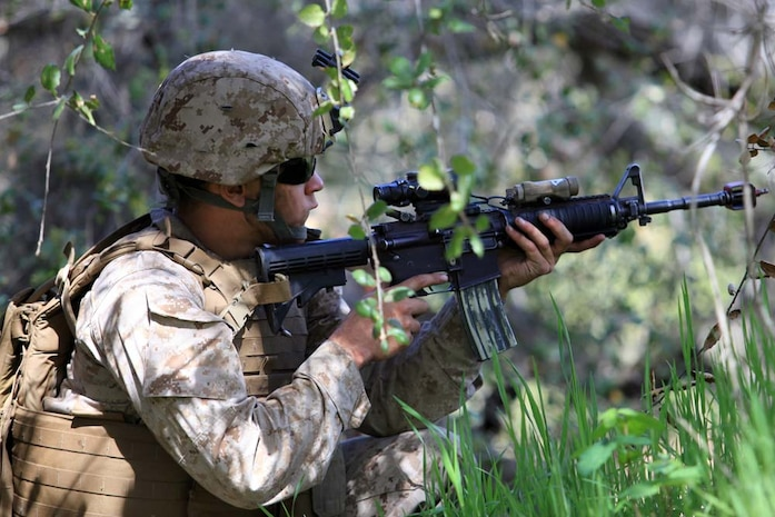 A Navy corpsman with 1st Battalion, 4th Marine Regiment, 1st Marine Division, provides security while Marines rescue a simulated downed pilot during Tactical Rescue of Aircraft Personnel training, at Camp Pendleton, March 21. During the TRAP mission instructors with Special Operations Training Group observed and monitored how the Marines reacted to multiple combat scenarios. The TRAP mission provides Marines with real world scenarios to prepare them for deployment.