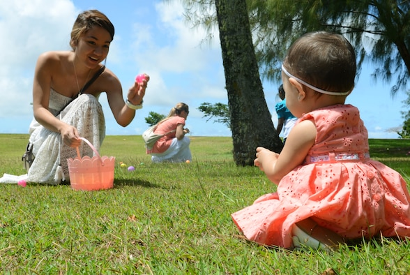 Brianna Lujan helps her daughter gather plastic eggs during the 554th RED HORSE Squadron Egg-stravaganza on Andersen Air Force, Guam, March 23, 2013. The squadron function was a combined information fair, potluck lunch and children's Easter egg hunt planned by the unit's spouses to help families of deployed military members celebrate the season and expose them to many of the base's support programs. (U.S. Air Force photo by Senior Airman Benjamin Wiseman/Released)