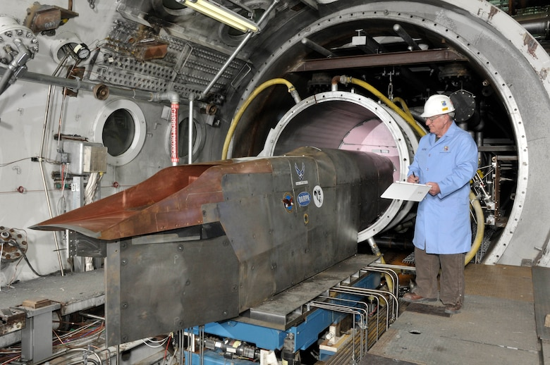 An Aerospace Testing Alliance outside machinist inspects the Defense Advanced Research Projects Agency's Falcon Combined-cycle Engine Technology (FaCET) scramjet test article in the center's Aerodynamic and Propulsion Test Unit test cell prior to a test. (Photo by Rick Goodfriend)