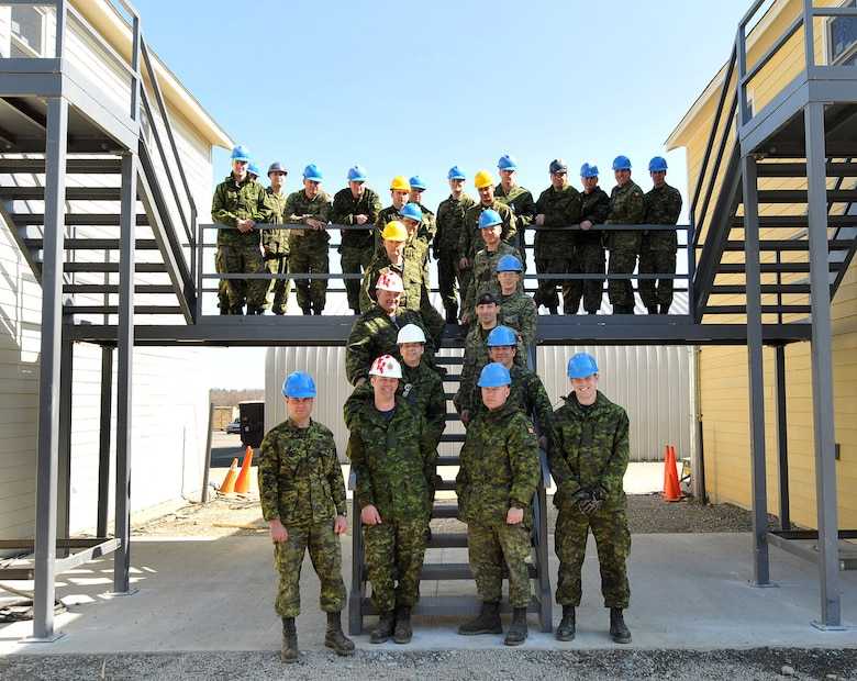 NEW LONDON,   N.C.  – In March 2013, 26 members of the Royal Air Force 3 Wing Construction Engineers Canadian Forces from Bagotville, Quebec, take time out for a photo on stairs installed between two buildings they constructed to be used for sleeping quarters and classrooms.  The Canadians were at the North Carolina Air National Guard Regional Training Site in New London, N.C., participating in the Deployment for Training Program hosted by 145th Civil Engineering Squadron.  This program is an exchange agreement between the Royal Canadian Air Force and the United States Air National Guard.  (National Guard Photo by Tech. Sgt. Patricia Findley, 145th Public Affairs)