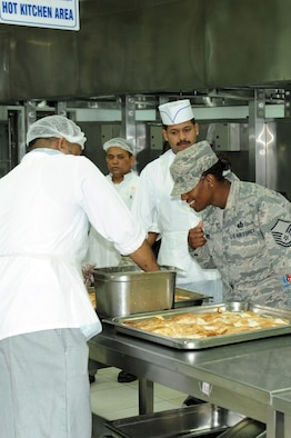 Master Sgt. Rayshawnda Davis, 386th Expeditionary Force Support Squadron, interacts with Third Country National employees in the Desert Winds dining facility at the 386th Air Expeditionary Wing, Southwest Asia Mar 19, 2013. Davis oversees all food operations at the 386th Air Expeditionary Wing and the 387th Air Expeditionary Group.