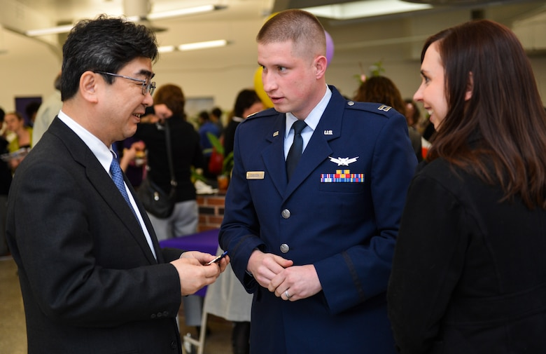 Capt. Joshua Carlson, 1st Space Operations Squadron mission commander, presents Ikuhiko Ono, Consul General of Japan, with a unit coin during his visit at a Kizuna Project event March 22, 2013, at Littleton High School, Littleton, Colo. The event was hosted so the Consul General of Japan could thank military service members who participated in Operation Tomodachi. Operation Tomodachi was a relief mission conducted in Japan following the 2011 earthquake and tsunami disaster. (U.S. Air Force photo by Senior Airman Paul Labbe/Released)