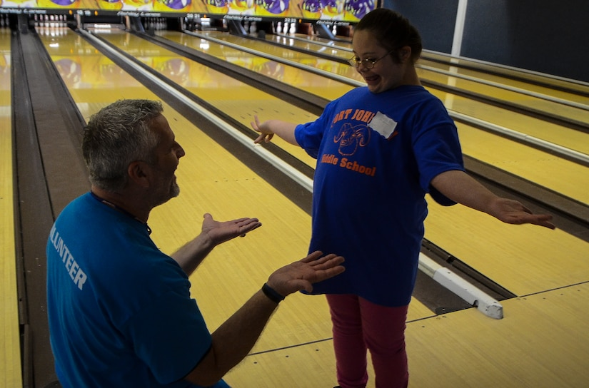 John Downey, spouse of Master Sgt. Dawn Downey, 628th Medical Group, congratulates a Special Olympian during the Special Olympics South Carolina Area 6 Bowling Event March 22, 2013, event in West Ashley, S.C. More than 15 Airmen and civilians from Joint Base Charleston volunteered to assist 35 middle school students. The children were from Zucker Middle School, Morningside Middle School, Fort Johnson Middle School and St. Andrews Middle School. (U.S. Air Force Photo/Airman 1st Class Jared Trimarchi)