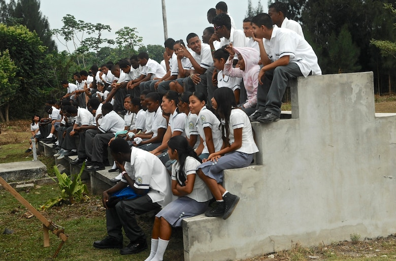 Students at Ladyville Technical High School assemble on a bleacher before the New Horizons 2013 opening ceremony at the school March 25, 2013. New Horizons is an exercise led by U.S. Southern Command that provides medical and dental treatment as well as constructs school structures throughout Belize. It gives U.S., Belizean and Canadian service members the opportunity to train side-by-side in an exercise setting, in order to be prepared to meet future challenges when and where needed. (U.S. Air Force photo/Master Sgt. James Law)