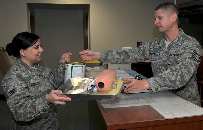Tech. Sgt. Tony Anderson, right, 51st Civil Engineer Squadron Mongrel Self Help Store NCO in charge,  gives paint supplies to Senior Airman Kimberlie Weiss, 51st CES operations support section customer service representative, at the Mongrel Self Help Store in Bldg. 657 on Osan Air Base, Republic of Korea, March 28. Airmen and dependents can utilize the self-help store for items needed to repair minor issues in dorms and base facilities. (U.S. Air Force photo/Senior Airman Kristina Overton)