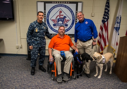 Commander Chadwick Bryant, Naval Consolidated Brig Charleston commander, and Rick Hairston, Canines for Service president, present service dog Malachi (black Labrador) to Rick Hayes, an Air Force veteran, during a ceremony March 21, 2013, at the Naval Consolidated Brig Charleston on Joint Base Charleston – Weapons Station, S.C. CFS is a non-profit health and human services organization that trains service dogs for people with disabilities. Through this program, military prisoners are taught to train service dogs for veterans with disabilities. Since the program's inception, 15 wounded service members have received service dogs. Service dogs are constant companions and can assist veterans with more than 70 tasks, including retrieving and carrying objects, opening doors, and helping with stress and balance difficulties.. (U.S. Air Force photo/ Senior Airman George Goslin)