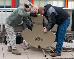 Air Force Maj. Jennifer Ferrau, Paul Noel and Tom Mullican, Joint Public Affairs Support Element (JPASE) members, work together to setup the satellite antenna to the Defense Video and Imagery Distribution System (DVIDS). The JPASE team deployed to the New York area in support of Hurricane Sandy relief.