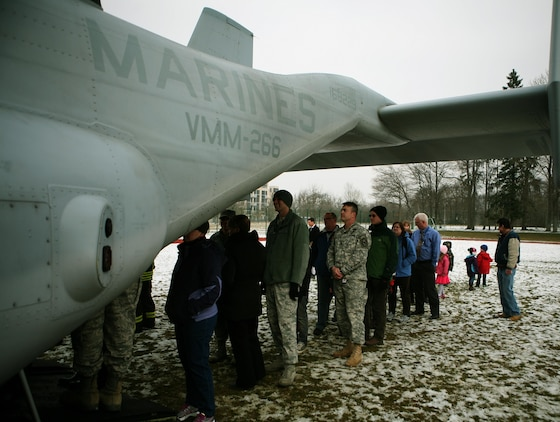 "Members from the U.S. Army Garrison Stuttgart, Germany, community wait in line to tour the inside of an MV-22B Osprey from Marine Tiltrotor Squadron 266 (Reinforced), 26th Marine Expeditionary Unit, II Marine Expeditionary Force, Camp Lejeune, N.C., during a capabilities demonstration at Kelly Barracks, March 28. U.S. Marine Corps Forces Europe, U.S. Marine Corps Forces Africa, in coordination with U.S. European Command, U.S. Africa Command, the community of U.S. Army Garrison Stuttgart, Germany, received  ""hands-on"" experience with the MV-22B Osprey during a capabilities exercise on Patch Barracks, Kelley Barracks, and Stuttgart Army Airfield, that helped to familiarize the combatant commands with the possibilities and new abilities the aircraft could provide throughout their respective area of reach. The three MV-22 Osprey crews flew 1400 nautical miles from the Atlantic Ocean, without having to land to refuel, before arriving two days earlier. The MV-22 Osprey possess twice the speed, can fly twice as high, carry three times the payload, and travels five times the distance of other legacy, medium-lift helicopters."