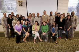 Service members and spouses of Headquarters and Support Battalion and Security and Emergency Services Battalion take a group photo during a Spouse Readiness Seminar, where twenty-one spouses learned about a variety of topics related to military life, here March 28.