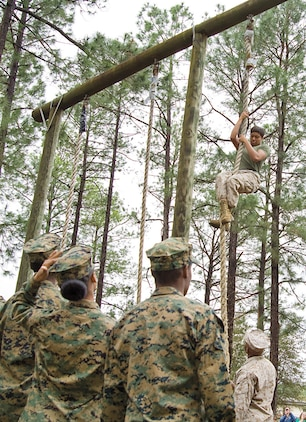 Marines demonstrate how to properly climb the obstacle course's rope climb to Marine and Navy Junior Reserve Officer Training Corps cadets here, March 19. The students put their training to the test by attempting all the course's obstacles with Marines right by their side.