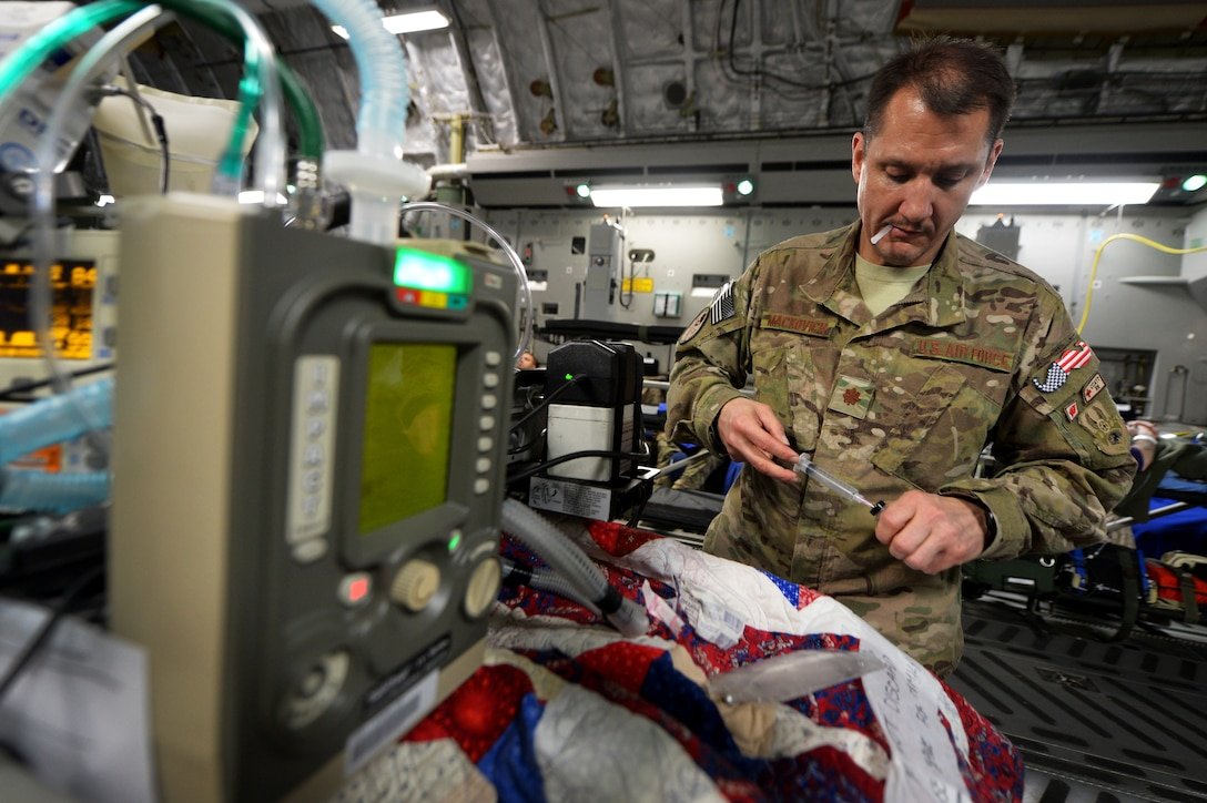 Maj. Michael Mackovich, 455th Expeditionary Aeromedical Evacuation Squadron Critical Care Air Transport Team nurse, prepares to administer intravenous medication during flight out of Bagram Airfield, Afghanistan, March 21, 2013. The CCATT crew is constantly on their feet during the flight to observe and interact with the patients for any signs of medical need. (U.S. Air Force photo/Senior Airman Chris Willis)