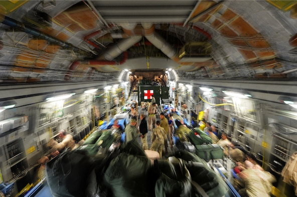 Members of the of the 455th Expeditionary Aeromedical Evacuation Squadron assist patients on a C-17 Globemaster III medical transport flight out of Bagram Airfield, Afghanistan, March 21, 2013. With help from the Critical Care Air Transport Team, the crew can turn a regular medical transport aircraft into a flying intensive care unit, making it possible to move severely injured or gravely ill servicemembers by air. (U.S. Air Force photo/Senior Airman Chris Willis)