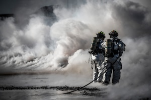 Firefighters from the 366th Civil Engineer Squadron extinguish a fire during a fire training exercise March 4, 2013, at Mountain Home Air Force Base, Idaho. Two teams worked in unison to push the fire back without it reigniting behind them. The training exercise was one component of a base-wide operational readiness exercise. (U.S. Air Force photo/Tech. Sgt. Samuel Morse)