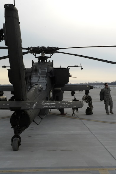 A U.S. Army AH-64 Apache Longbow crew chief from the 1-135th Attack Reconnaissance Battalion at Whiteman Air Force Base, Mo., prepares his aircraft March 27, 2013, for its deployment to Afghanistan. The 1-135th ARB will be working primarily with combat operations. (U.S. Air Force photo by Airman 1st Class Shelby R. Orozco/Released)