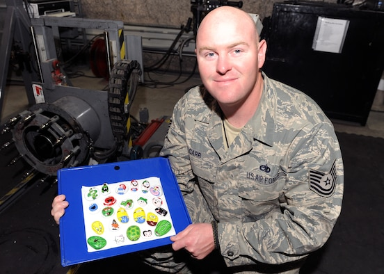 Tech. Sgt. Christopher Carr started an art collection by painting rocks found on the desert floor and leaving them for service members to improve morale. Carr hopes his art will inspire others to do their own artwork, or leave an inspirational message if you're not an artist. Carr is an aircraft battle damage repair technician with the 379th Expeditionary Maintenance Squadron. Carr is deployed from Robins Air Force Base, Ga., and is a native of Birmingham, Ala. (U.S. Air Force photo/Senior Airman Joel Mease)
