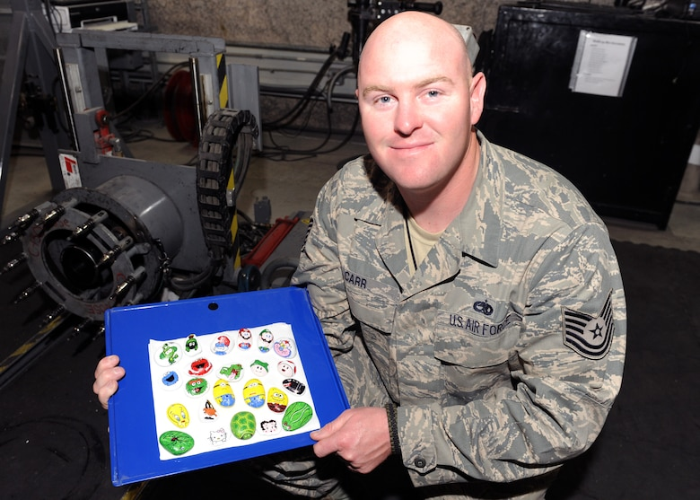"SOUTHWEST ASIA – Tech. Sgt. Christopher Carr, an aircraft battle damage repair technician with the 379th Expeditionary Maintenance Squadron, started an art collection by painting rocks found on the desert floor and leaving them for service members to improve morale. ""You could pick it up and take it with you, or maybe even lay it somewhere else for someone else to kick over and find,"" Carr said. ""Maybe it will inspire others to do their own artwork, or leave an inspirational message if you're not an artist."" Carr is deployed from Robins Air Force Base, Ga., and is a native of Birmingham, Ala. (U.S. Air Force photo/Senior Airman Joel Mease)"