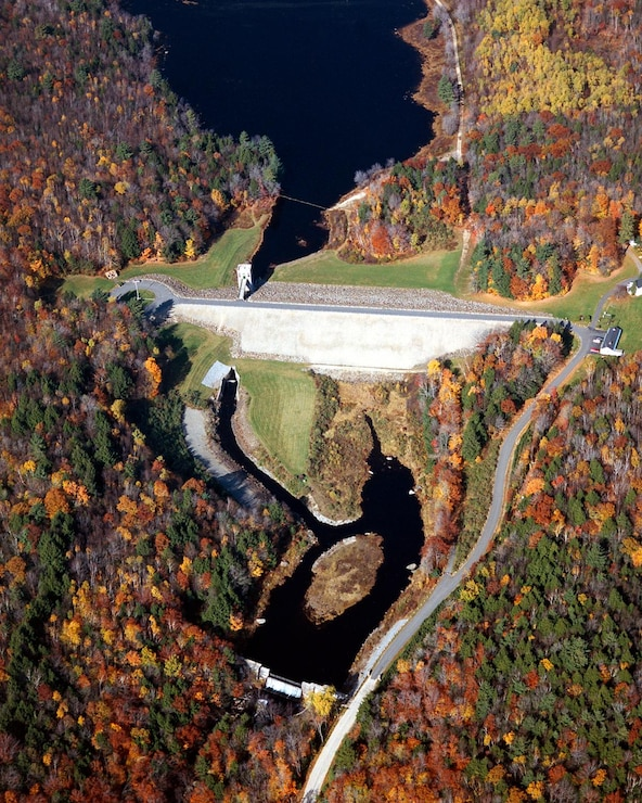 An aerial photo of the dam at Edward MacDowell Lake, taken in the fall. Edward MacDowell Dam is located on Nubanusit Brook. The dam protects Peterborough and other communities downstream and is part of five flood control dams in the Merrimack River Basin.