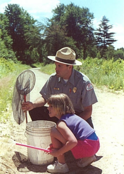 Park Ranger Jason Tremblay points out signs of life in a vernal pool to a young visitor during a pond interpretive program at Edward MacDowell Lake, Peterborough, N.H.