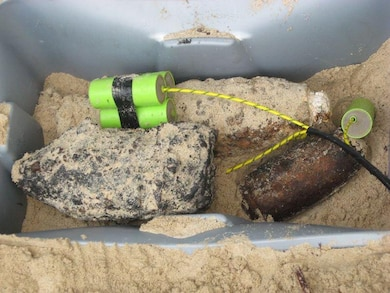 A 5-inch projectile and a BDU-33, along with other munitions that show the effects of time, are prepared for destruction during a Military Munitions Response Program site inspection at a Formerly Used Defense Site on Culebra, Puerto Rico's northwest peninsula.  The Military Munitions Support Services online workshops allow experts in the field to share best practices on sites like these and others around the U.S.