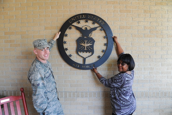 U.S. Air Force Airman 1st Class Westin Warburton, Air Force Public Affairs Agency photographer, displays a donated United States Air Force emblem with Ms. Ramona Lewis, Lackland Fisher Houses manager, at Joint Base San Antonio-Lackland, Texas, March 25, 2013. The average stay at a Fisher House is 16 days and the longest stay is 358. (U.S. Air Force photo by Senior Airman Grovert Fuentes-Contreras)