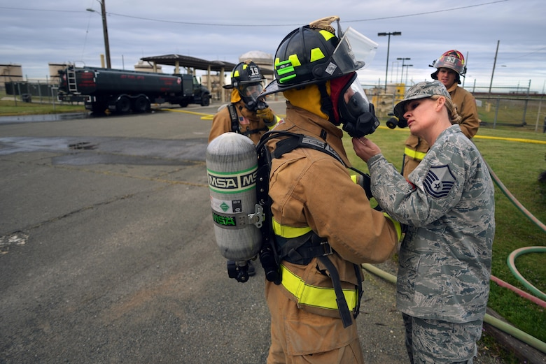 Master Sgt. Gina Ennis, 9th Civil Engineering Squadron fire emergency services flight, ensures protection equipment is properly donned on emergency responders during a simulated fuel spill on Beale Air Force Base, Calif., March 28, 2013.(U.S. Air Force photo by Airman 1st Class Drew Buchanan/Released)