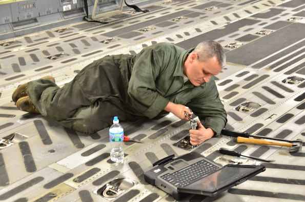 WRIGHT-PATTERSON AIR FORCE BASE, Ohio - Master Sgt. Ty Walk, 445th Maintenance Squadron aerospace repair craftsman, makes repairs to the floor in the cargo area of a C-17 Globemaster III during a routine Home Station Check inspection Feb. 21. (U.S. Air Force photo/Stacy Vaughn)
