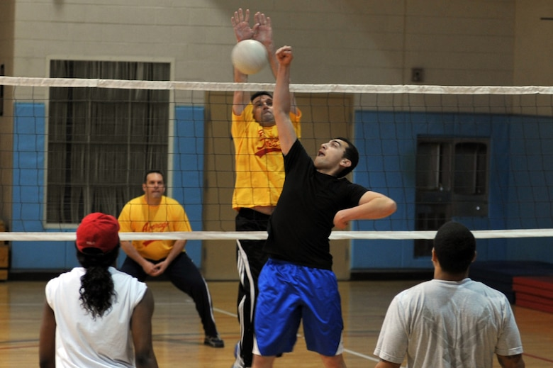 Command Chief Master Sergeant Scott Delveau (left), 7th Air Force command chief, blocks a spike from Senior Airman Jeffery Bowen, 51st Maintenance Squadron member, in the Battle of the Tiers volleyball tournament at the Osan Fitness Center on Osan Air Base, Republic of Korea, March 29, 2013. The Chiefs Group eliminated the Osan Junior Enlisted Council in the tournament. (U.S. Air Force photo/Senior Airman Alexis Siekert)