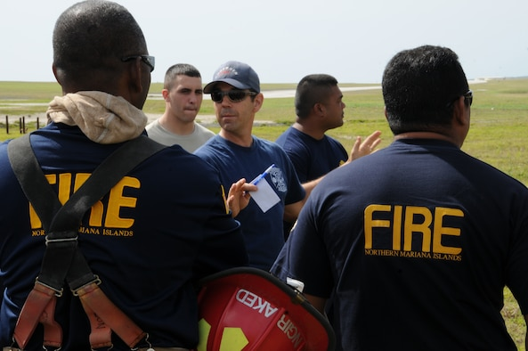 Jason Crandall, 36th Civil Engineer Squadron Fire and Emergency Services crew chief, briefs Andersen and Saipan fire personnel before a structural fire exercise on Andersen Air Force Base, Guam, March 27, 2013. Andersen Fire and Emergency Services personnel hosted four Saipan fire officers for joint fire training during their visit to Guam March 25-29. (U.S. Air Force photo by Staff Sgt. Melissa B. White/Released)